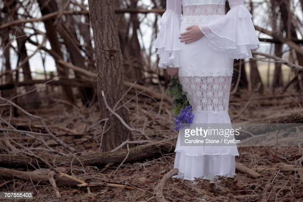Low Section Of Bride Holding Purple Flowers By Bare Trees In Forest