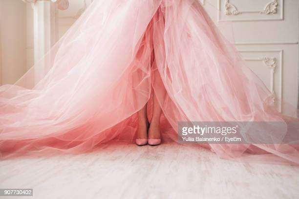 low section of bride wearing peach wedding dress in bridal shop - evening gown stock photos and pictures