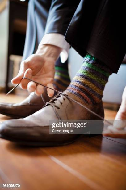low section of bridegroom tying shoelace at home - tying shoelace stock pictures, royalty-free photos & images
