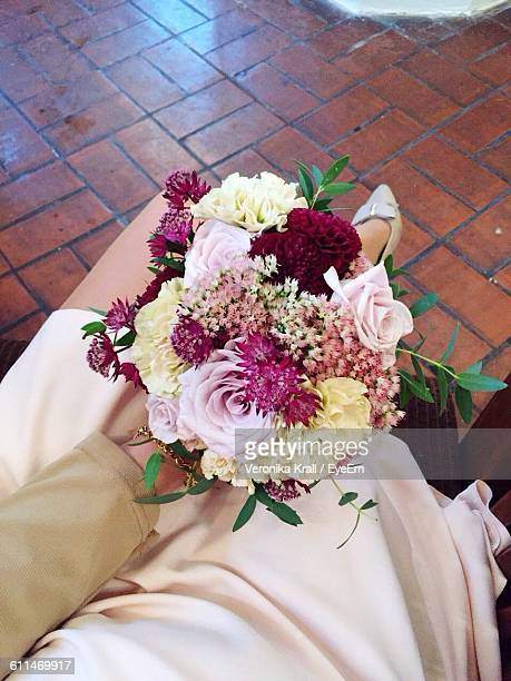 Low Section Of Bridesmaid Sitting With Colorful Bouquet