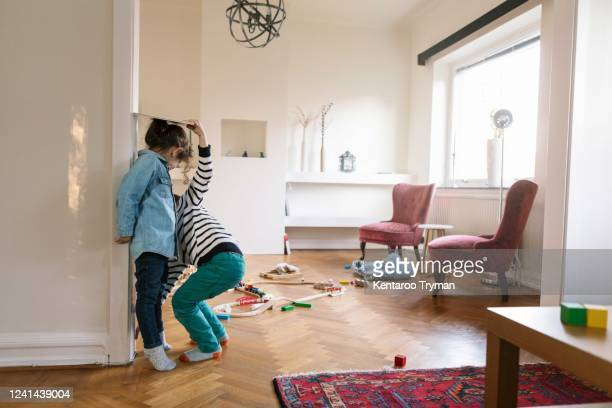 low section of brother measuring sister's height on wall with book at home - sibling stock pictures, royalty-free photos & images