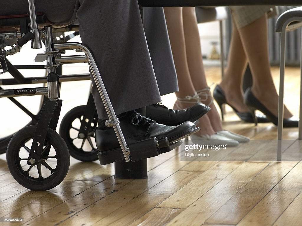 Low Section of Business Men and Women, Man Sitting in a Wheelchair : Stock Photo