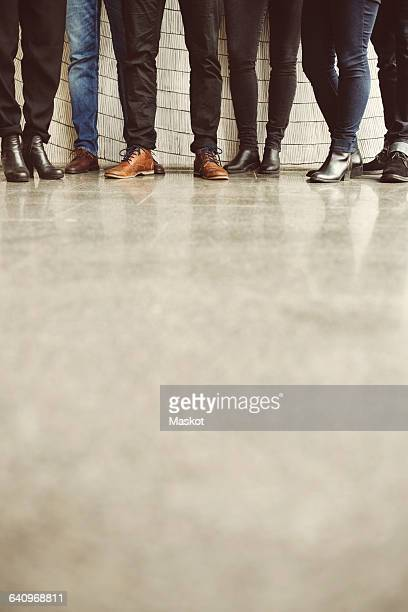 Low section of business people wearing jeans at office
