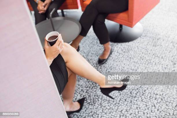 Low section of business women sitting and drinking coffee