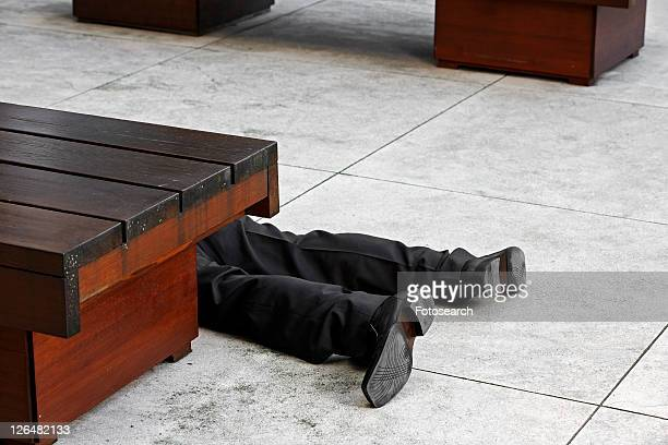 Low Section of Businessman Lying on Tiled Floor