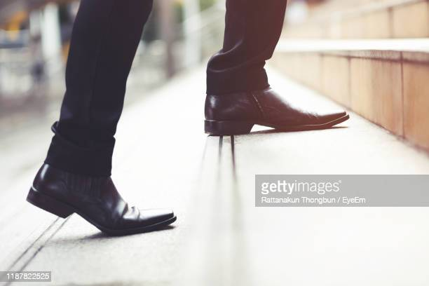 low section of businessman moving up on steps - nette schoen stockfoto's en -beelden