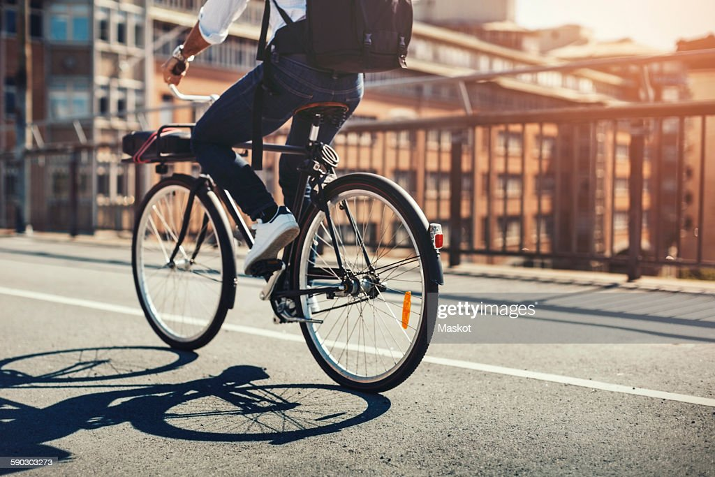 Low section of businessman riding bicycle on bridge in city : ストックフォト