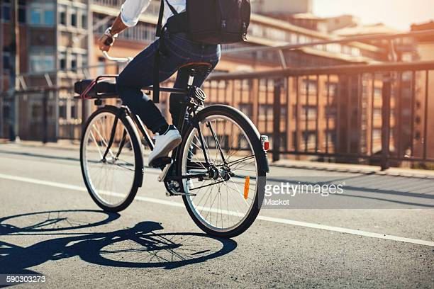 Low section of businessman riding bicycle on bridge in city