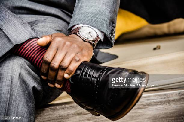 low section of businessman sitting on bench - nette schoen stockfoto's en -beelden