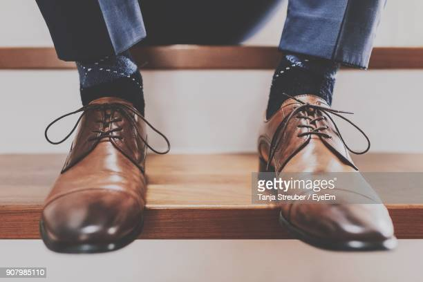 low section of businessman sitting on steps - work shoe stock photos and pictures