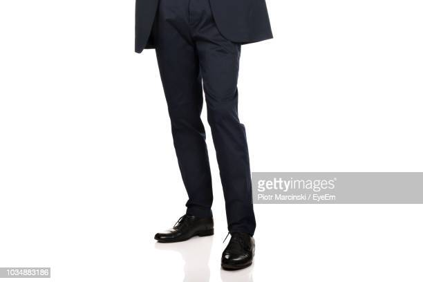 low section of businessman standing against white background - sapato preto - fotografias e filmes do acervo