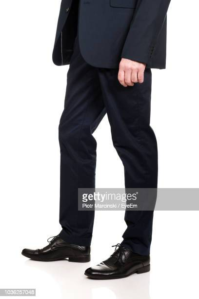 low section of businessman standing against white background - low section stock pictures, royalty-free photos & images