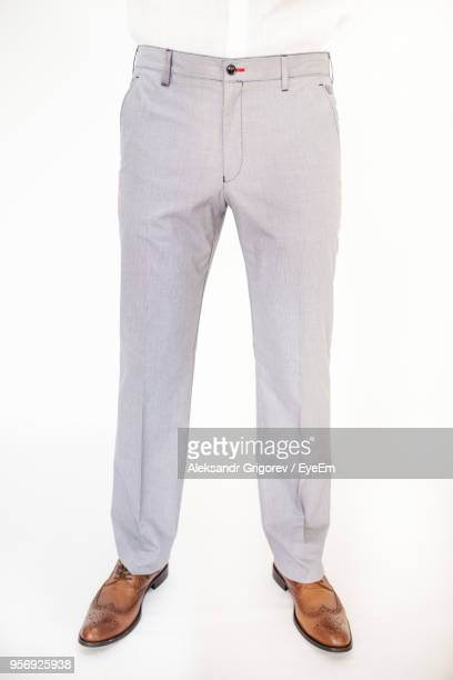 low section of businessman standing against white background - trousers stock pictures, royalty-free photos & images