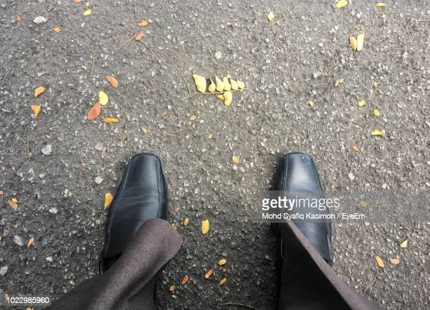 low section of businessman standing on road - dress shoe stock pictures, royalty-free photos & images