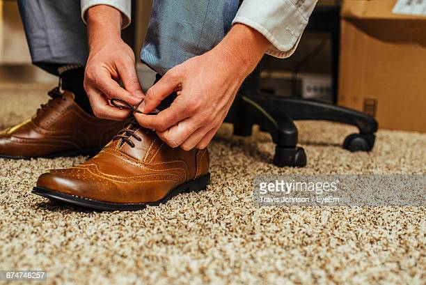 low section of businessman tying shoes in office - brown shoe stock photos and pictures