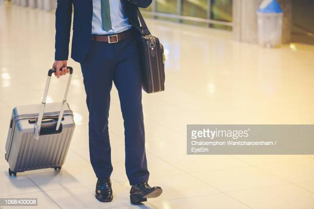 low section of businessman with luggage walking at airport - wheeled luggage stock photos and pictures