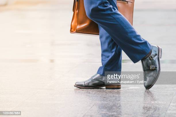 low section of businessman with suitcase walking on street - calzature di pelle foto e immagini stock