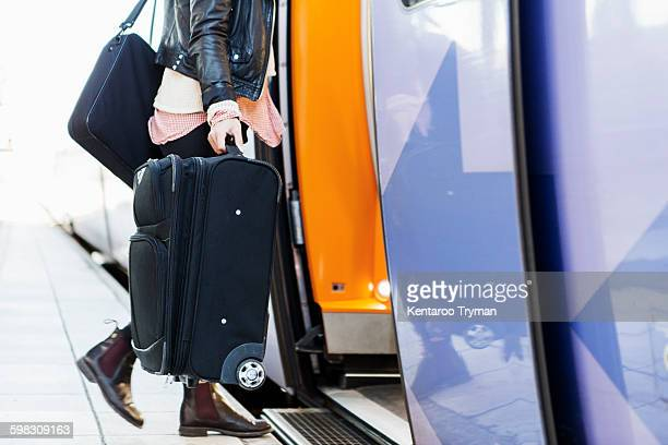 Low section of businesswoman carrying luggage while boarding train at railway station