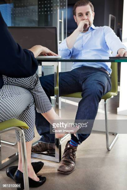 low section of businesswoman playing footsie with male colleague at conference table - playing footsie stock photos and pictures