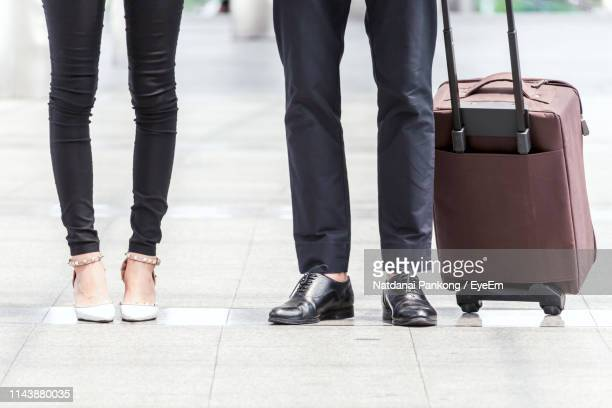 low section of businesswoman standing by colleague holding luggage on footpath - mens dress shoes stock pictures, royalty-free photos & images