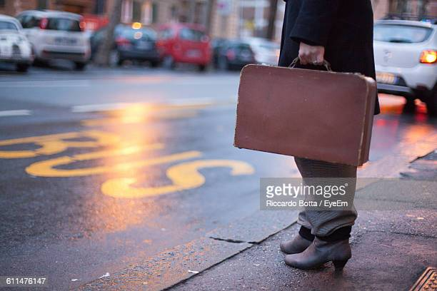 Low Section Of Businesswoman Standing On Footpath By Street