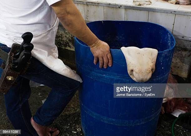 Low Section Of Butcher Standing By Blue Container At Slaughterhouse