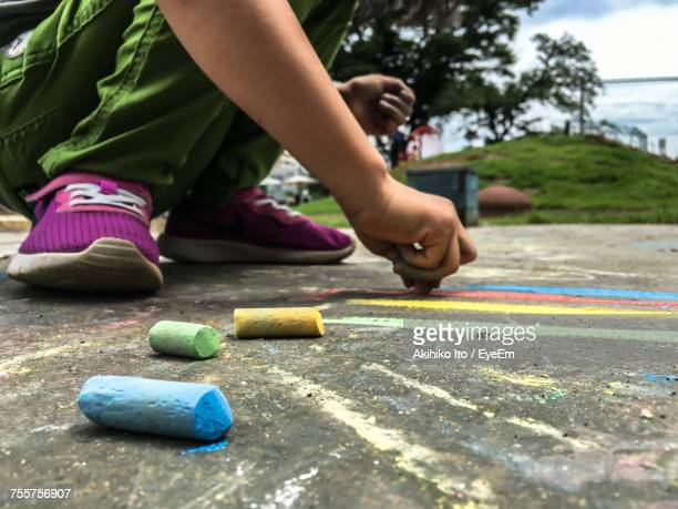 Low Section Of Child Drawing On Asphalt
