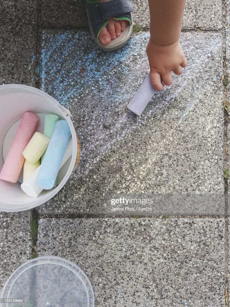 Low Section Of Child Holding Chalk While Drawing On Footpath : Photo