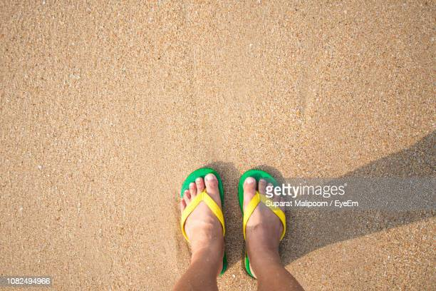 low section of child in flip-flop standing at shore - flip flop stock pictures, royalty-free photos & images