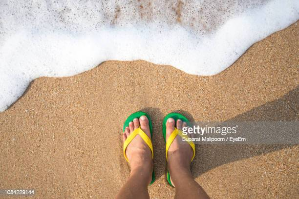 low section of child in flip-flop standing at shore - areia - fotografias e filmes do acervo