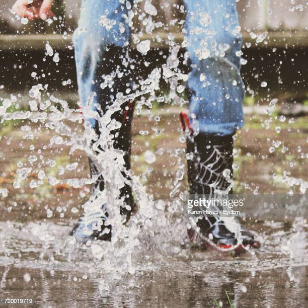 Low Section Of Child Jumping In Puddle