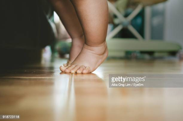 Low Section Of Child On Floor At Home