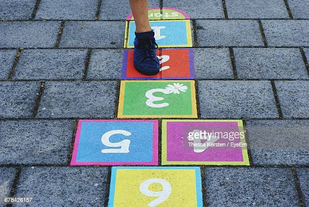 low section of child playing hopscotch on footpath - hopscotch stock photos and pictures