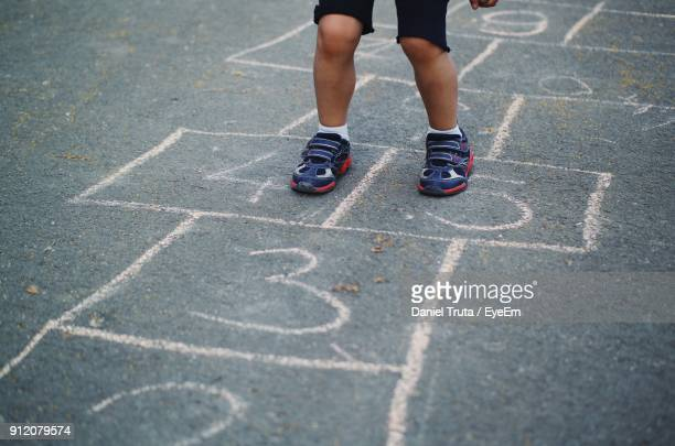 low section of child playing hopscotch on road - hopscotch stock pictures, royalty-free photos & images