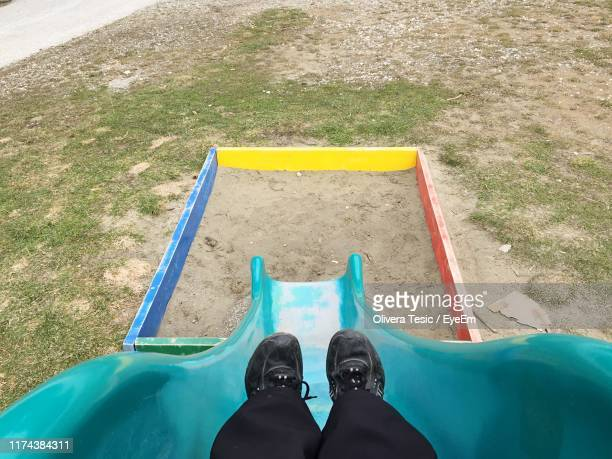 low section of child sliding in playground - slide play equipment stock pictures, royalty-free photos & images