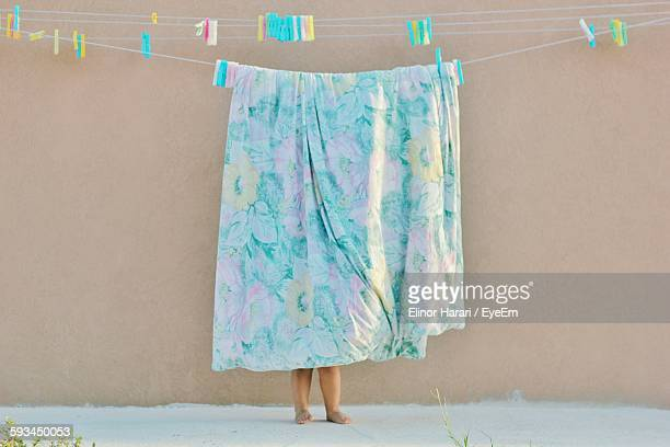 Low Section Of Child Standing Behind Sheet Drying On Clothesline
