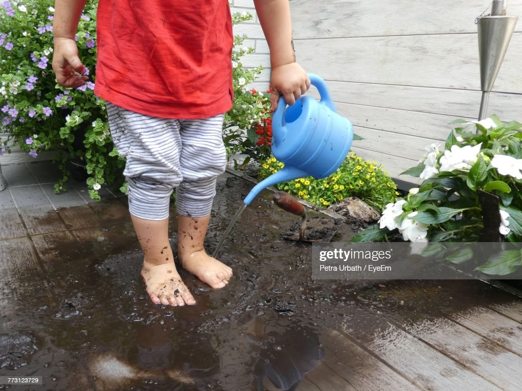 Low Section Of Child Standing On Deck With In Mud : Stock Photo