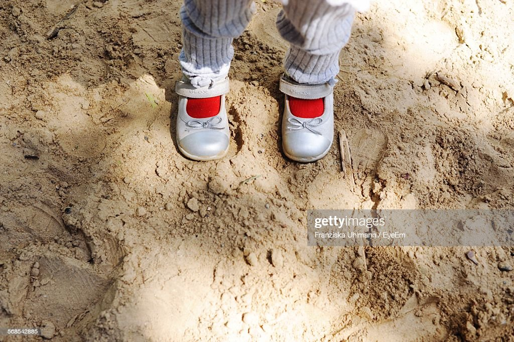 Low Section Of Child Standing On Sandy Field : Stock Photo