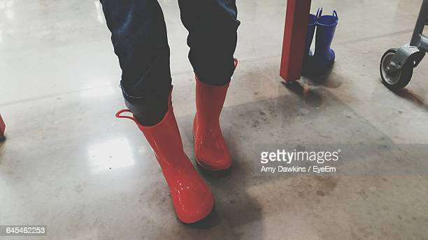 Low Section Of Child Wearing Red Boots Standing On Floor
