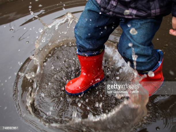 low section of child wearing rubber boots jumping in puddle during monsoon - igor golovniov stock pictures, royalty-free photos & images