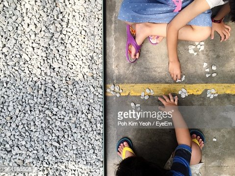 Low Section Of Children Playing With Gravels While Sitting On Road