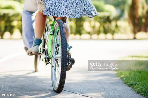 low section of couple cycling on road - tandem bicycle stock pictures, royalty-free photos & images
