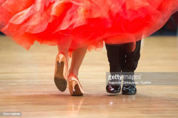 low section of couple dancing on hardwood floor - danse latine photos et images de collection