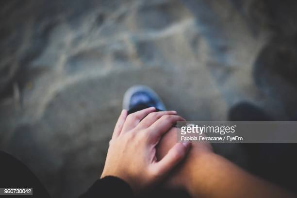 low section of couple holding hands at beach - man touching womans leg stock photos and pictures