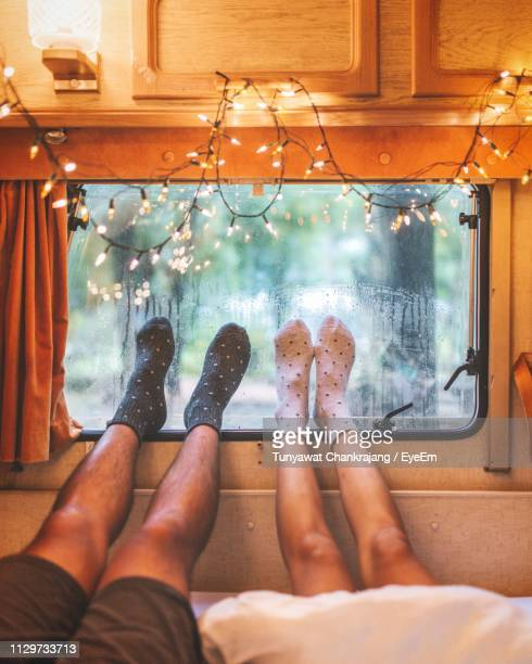low section of couple relaxing in motor home - subjektive kamera ungewöhnliche ansicht stock-fotos und bilder