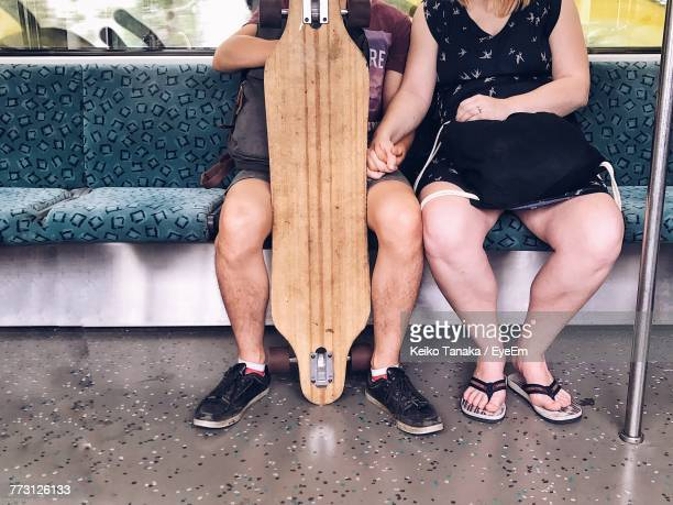 Low Section Of Couple Sitting On Sofa In Train
