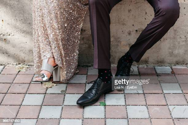 low section of couple sitting outdoors - dress shoe stock pictures, royalty-free photos & images