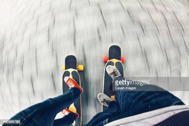 Low section of couple skateboarding on road