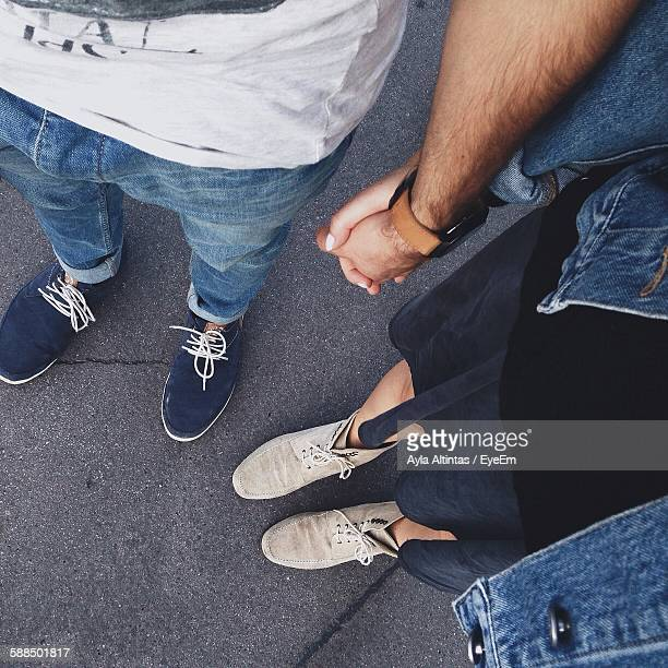Low Section Of Couple Standing On Street