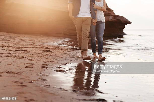 Low Section Of Couple Walking On Beach